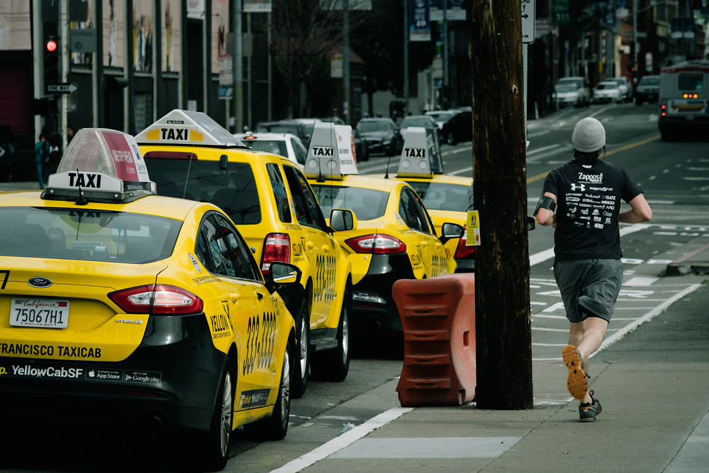 Taxis and a runner